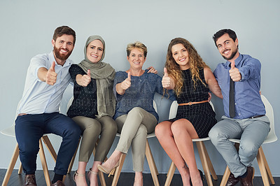 Buy stock photo Portrait of a group of cheerful businesspeople seated next to each other while showing thumbs up
