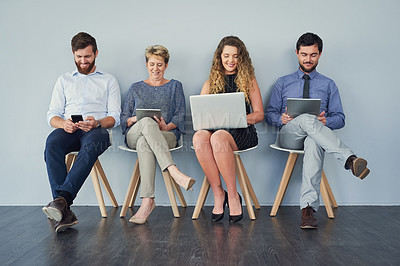 Buy stock photo Studio shot of a group of businesspeople using their wireless devices while being seated against a grey background