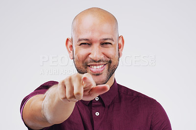 Buy stock photo Portrait of a handsome young man pointing towards the camera against a grey background
