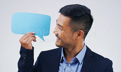 Buy stock photo Shot of a handsome young businessman holding a speech bubble against a grey background