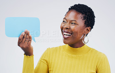 Buy stock photo Shot an attractive young woman looking surprised while holding a speech bubble against a grey background
