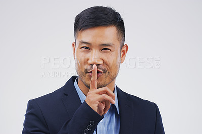 Buy stock photo Portrait of a handsome businessman posing with his finger on his lips against a grey background