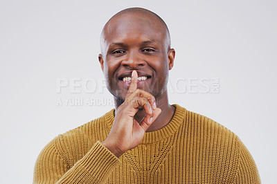 Buy stock photo Portrait of a handsome young man posing with his finger on his lips against a grey background