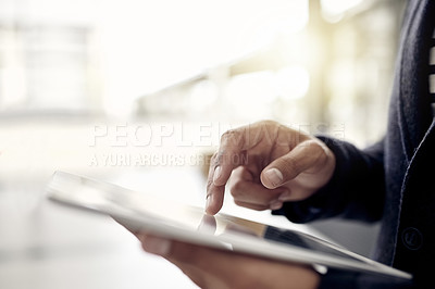 Buy stock photo Closeup shot of an unrecognizable businessman using a digital tablet in an office