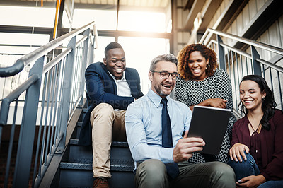Buy stock photo Low angle shot of a diverse group of colleagues having an impromptu meeting with a tablet on the stairs