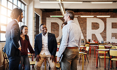 Buy stock photo Cropped shot of a team of laid-back businesspeople chatting during their break in the office