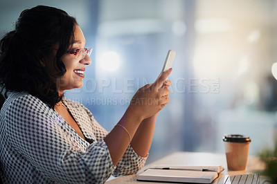 Buy stock photo Shot of a young businesswoman using a cellphone while working in an office at night