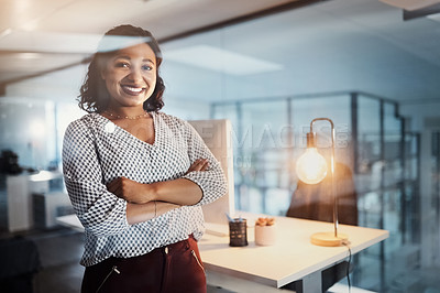Buy stock photo Portrait of a young businesswoman standing in an office at night