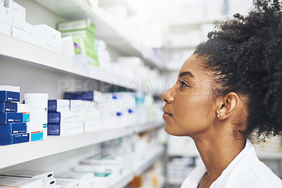 Buy stock photo Shot of a female pharmacist looking at the shelves in a chemist
