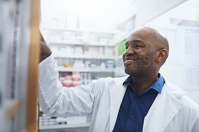 Buy stock photo Shot of a pharmacist looking for something on the shelves