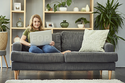 Buy stock photo Full length shot of an attractive young woman using her laptop while relaxing on the sofa at home