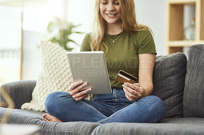 Buy stock photo Cropped shot of an attractive young woman shopping online using her tablet while relaxing on the sofa at home
