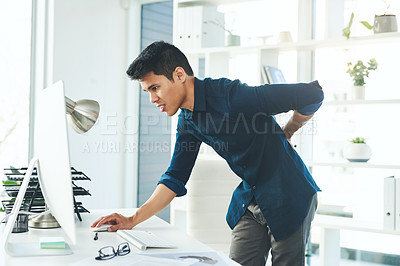 Buy stock photo Shot of a young businessman experiencing back pain while working in a modern office