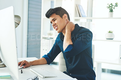 Buy stock photo Shot of a young businessman experiencing neck pain while working in a modern office