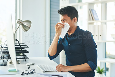 Buy stock photo Shot of a young businessman blowing his nose with a tissue while working in a modern office