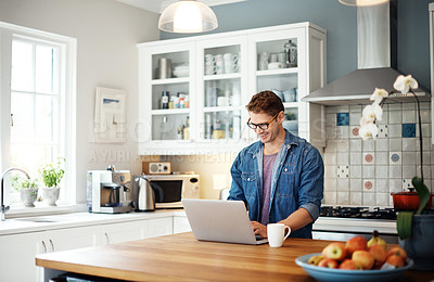 Buy stock photo Cropped shot of a man using his laptop while sitting in his kitchen
