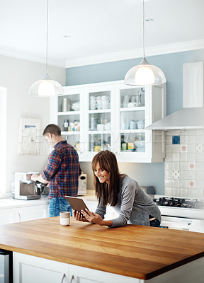 Buy stock photo Shot of a woman using a digital tablet with her boyfriend standing in the background