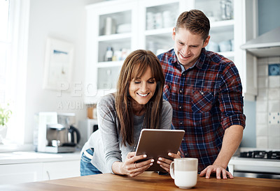 Buy stock photo Cropped shot of a middle aged couple looking at something on a digital tablet