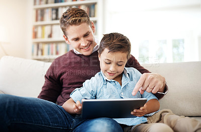 Buy stock photo Shot of a little boy browsing on a digital tablet while sitting with his father