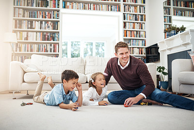 Buy stock photo Shot of a man spending quality time with his two kids at home