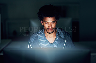 Buy stock photo Shot of a young businessman using a computer during a late night at work