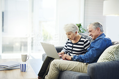 Buy stock photo Shot of senior couple using a laptop together on the sofa at home
