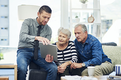 Buy stock photo Shot of senior couple using a digital tablet during a consultation with a financial advisor at home