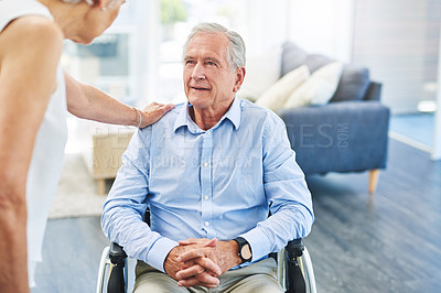 Buy stock photo Shot of a senior man in a wheelchair being cared for by his wife at home