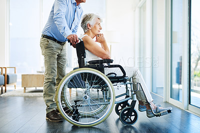 Buy stock photo Shot of a senior woman in a wheelchair looking out a window with her husband at home