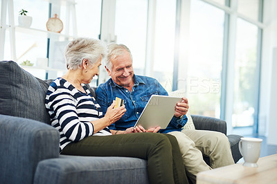 Buy stock photo Shot of a senior couple using a digital tablet and credit card while relaxing together on the sofa at home