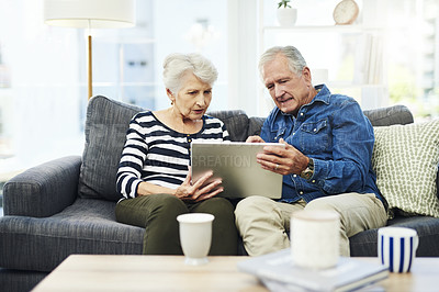 Buy stock photo Shot of senior couple using a digital tablet together on the sofa at home