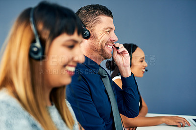 Buy stock photo Shot of a mature man working in a call centre alongside his colleagues