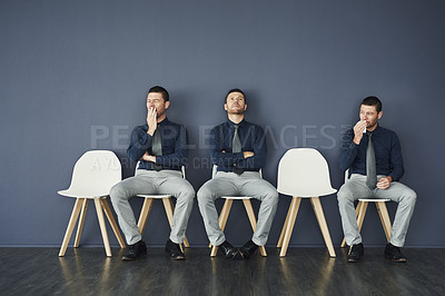 Buy stock photo Studio shot of a irritated young businessman being seated with two copies of himself while waiting for a interview
