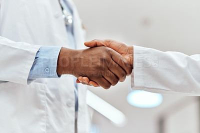 Buy stock photo Cropped shot of two unrecognizable chemists shaking hands while working in the pharmacy