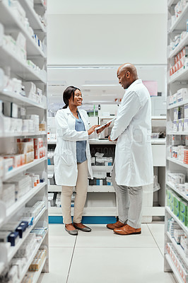 Buy stock photo Full length shot of two young chemists doing stock take while working in the pharmacy
