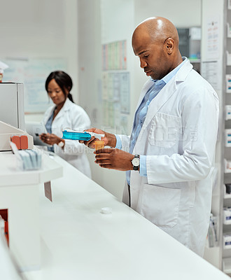 Buy stock photo Cropped shot of a handsome young male chemist working behind a counter in the pharmacy with a colleague in the background
