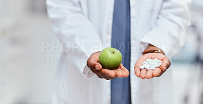 Buy stock photo High angle shot of an unrecognizable female chemist holding an apple and  medication while standing in the pharmacy
