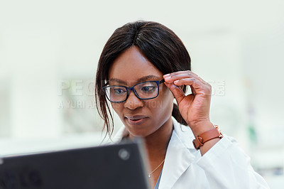 Buy stock photo Cropped shot of an attractive young chemist working the checkout counter at the pharmacy