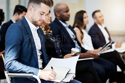 Buy stock photo Shot of a businessman making notes during a conference