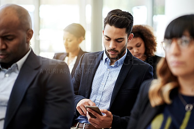 Buy stock photo Shot of a businessman using a smartphone during a conference