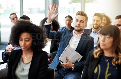 Buy stock photo Shot of a young businessman raising his hand to ask a question during a conference