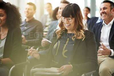 Buy stock photo Shot of a businesswoman making notes during a conference