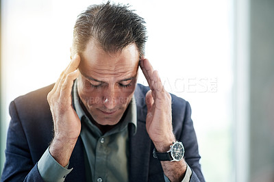 Buy stock photo Shot of a mature businessman experiencing stress at work