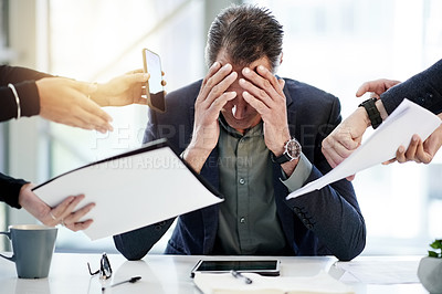 Buy stock photo Shot of a mature businessman looking stressed out in a demanding office environment