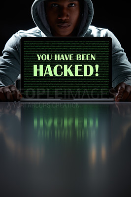"""Buy stock photo Shot of a young hacker using a laptop with the words """"You have been hacked"""" on it"""