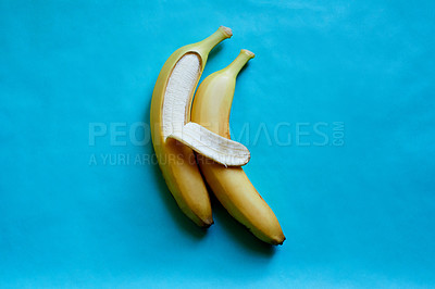Buy stock photo Studio shot of two bananas lying side by side in a suggestive position against a blue background