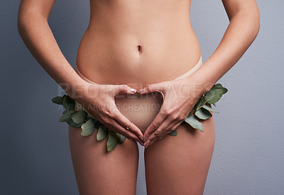 Buy stock photo Cropped studio shot of a woman wearing leafy underwear and making a heart shaped gesture against a grey background