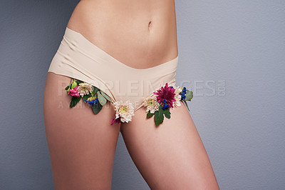 Buy stock photo Cropped studio shot of a slim woman wearing underwear with flowers sticking out of it against a grey background