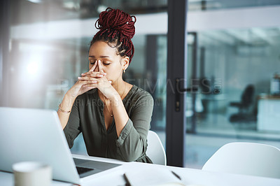 Buy stock photo Shot of a young businesswoman looking stressed out while working in an office