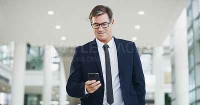 Buy stock photo Cropped shot of a mature businessman using a smartphone while walking through a modern office